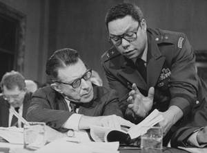 Defense Secretary Caspar Weinberger speaks with then MG Colin Powell during testimony before the Senate Budget Committee on Capitol Hill on 8 Feb 1985.