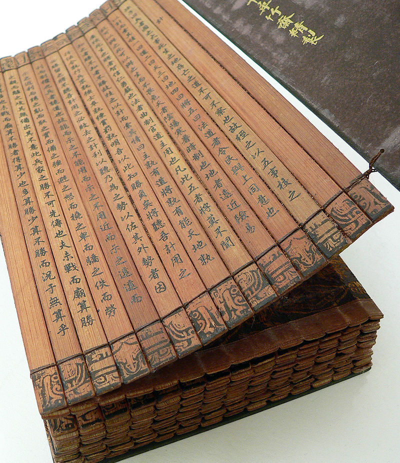 A Chinese bamboo book, open to display the binding and contents. This copy of The Art of War by Sun Tzu is part of a collection at the University of California, Riverside. (Wikimedia)