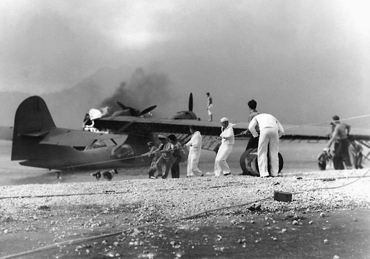 U.S. Navy sailors attempt to save a burning Consolidated PBY Catalina flying boat at Naval Air Station Kaneohe Bay on 7 December 1941. This plane was set afire by strafing in the the initial phase of the attack and was sunk in a later strike. Note dog observing the work. (U.S. Navy Photograph)