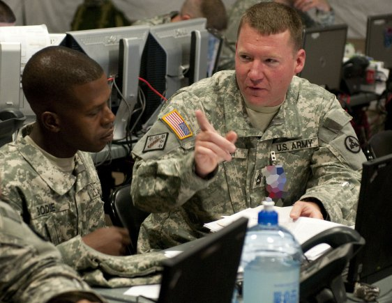 Sergeant First Class Johnathan Bodie and Timothy Inman discuss sustainment operations during the 3d Sustainment Command (Expeditionary) Command Post Exercise-Sustainment at Fort Lee, Va. (U.S. Army photo)