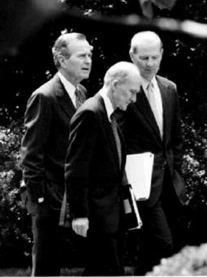 President George H.W. Bush speaks with National Security Advisor Brent Scowcroft and Secretary of State James Baker on May 19, 1992 (Photo Credit: David Ake/Getty)