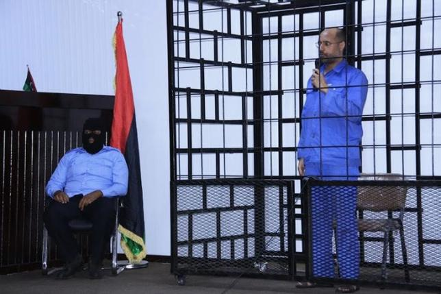 """We will win."" Saif al-Islam Gaddafi attends a hearing behind bars, June 22, 2014. (Reuters)"
