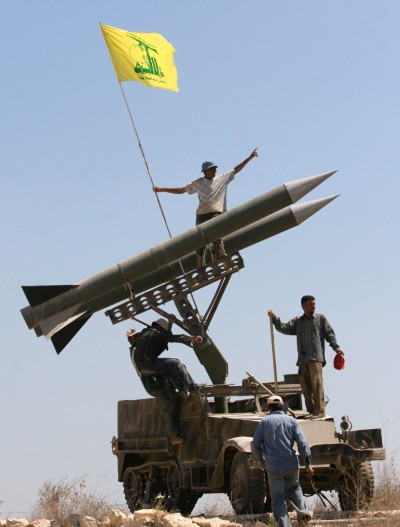Hezbollah supporters fix the party's flag on top of their rockets near the southern port city of Tyre, Lebanon  (Mohammed Zaatari / AP)
