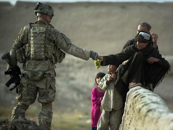 A U.S. soldier shares grapes with Afghan boys in the southern province of Kandahar. (Photo by Tony Karumba)