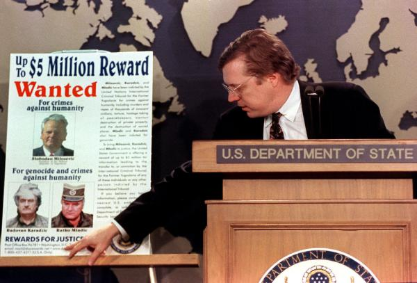 David Scheffer, U.S. ambassador-at-large for war crimes unveils a poster at the State Department in March 2000. The poster includes the images of Yugoslav President Slobodan Milosevic, Radova    n  Karadžić , and Ratko Mladic. (Rachel Griffith |UPI)
