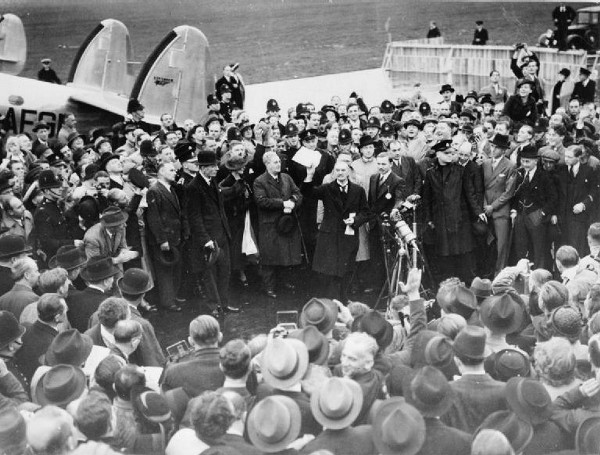"""Neville Chamberlain holding the paper containing the resolution to commit to peaceful methods signed by both Hitler and himselfon his return from Munich on 30 September 1938. Later that day, at 10 Downing Street, he remarked, """"My good friends, for the second time in our history, a British Prime Minister has returned from Germany bringing peace with honour. I believe it is peace for our time.""""(Wikimedia Commons)"""