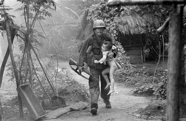 A U.S. infantryman from A Company, 1st Battalion, 16th Infantry carries a crying child from Cam Xe village after dropping a phosphorous grenade into a bunker cleared of civilians during an operation near the Michelin rubber plantation northwest of Saigon, August 22, 1966. A platoon of the 1st Infantry Division raided the village, looking for snipers that had inflicted casualties on the platoon. GIs rushed about 40 civilians out of the village before artillery bombardment ensued. (Via AP/NBCNews, Horst Faas)