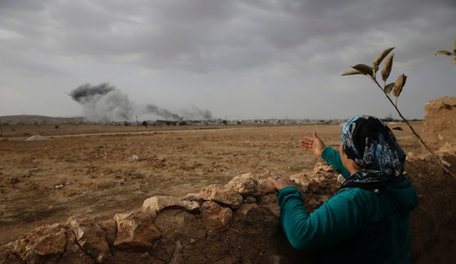 A Turkish Kurd on the Turkey-Syria border watches smoke over Kobani Syria Oct 12 2014 (AP)