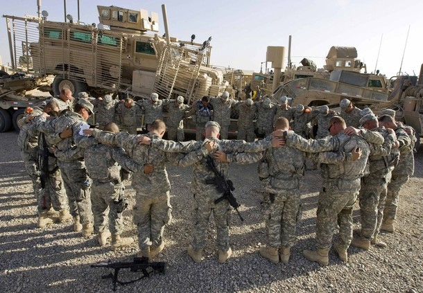 Soldiers of Army National Guard 162 Engineer Company attached with 2nd Combat Engineer Battalion of the USMC pray in front of their MRAP which was recently hit by road side bomb (Shamil Zhumatov/Reuters)