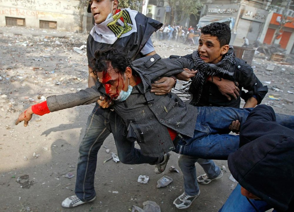Protesters carry an injured comrade during clashes in a side street near Tahrir Square in Cairo, on November 23, 2011. (Goran Tomasevic/Reuters)