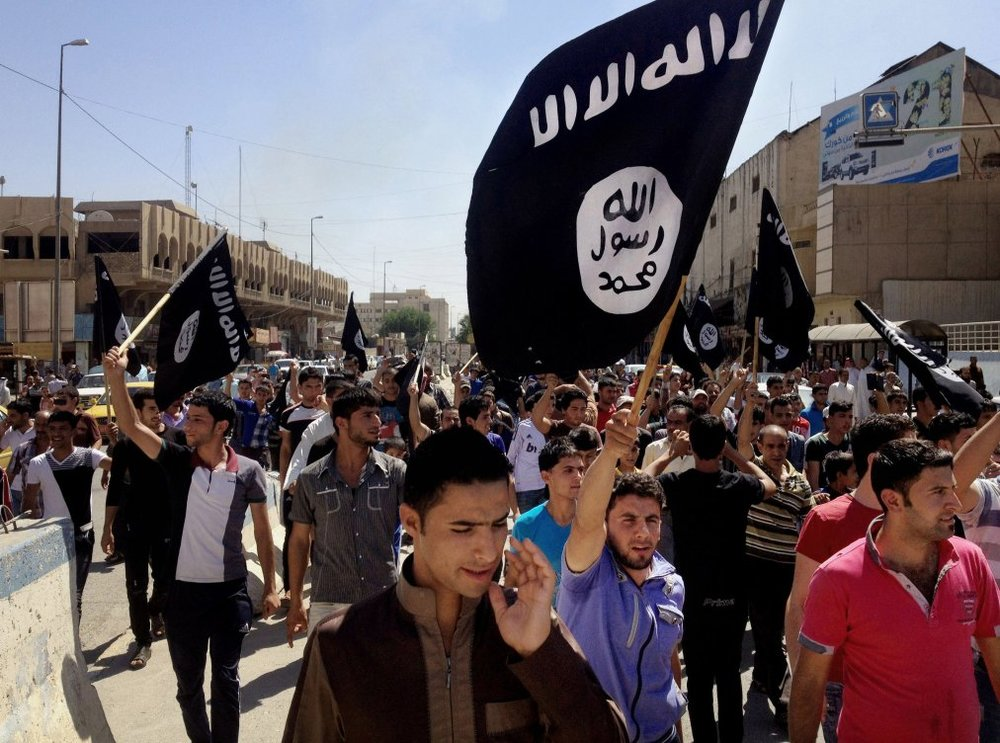 "On Monday, June 16, 2014, demonstrators chant pro-Islamic State group slogans as they wave the group's flags in front of the provincial government headquarters in Mosul, 225 miles (360 kilometers) northwest of Baghdad, Iraq. The declaration of a ""caliphate"" in Iraq and Syria inspired a stream of thousands of foreign fighters to join it and earned it pledges of allegiance by individual militants around the region. (AP Photo)"