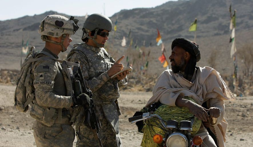 U.S. Army Sgt. Skyler Rosenberry of Pennsylvania (left) and an interpreter speak to an Afghan man in a village in Afghanistan. (AP)