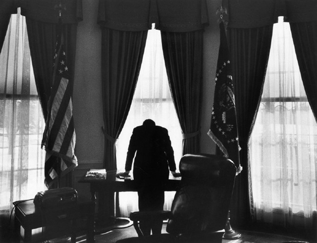 """The Loneliest Job,"" a photograph of President John F. Kennedy looking out of the south window of the oval office taken on 10 Feb 1961. (George Tames)"