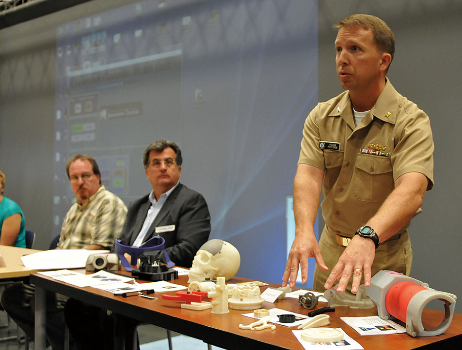 Captain Frank Futcher explains display of 3D-printed objects during Navy Warfare Development Command–sponsored innovation workshop at Old Dominion University in Norfolk, Virginia (Jonathan E. Donnelly/U.S. Navy Photo)
