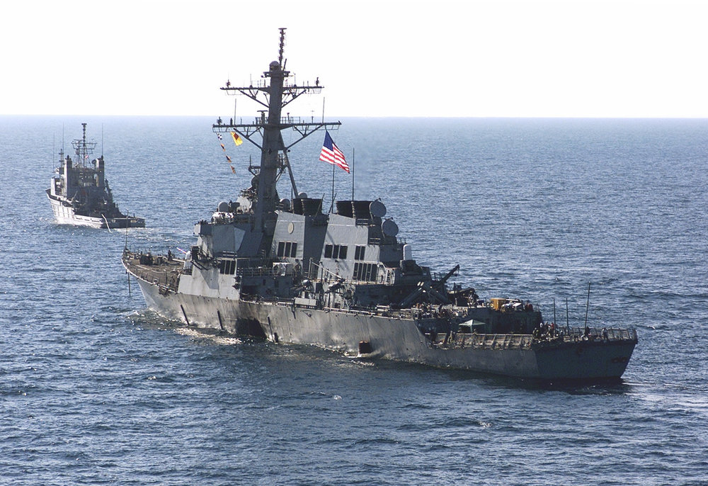 The USS Cole towed away from the port city of Aden, Yemen, into open sea by the tug USNS Catawba. (Sgt. Don L. Maes/USMC Photo)