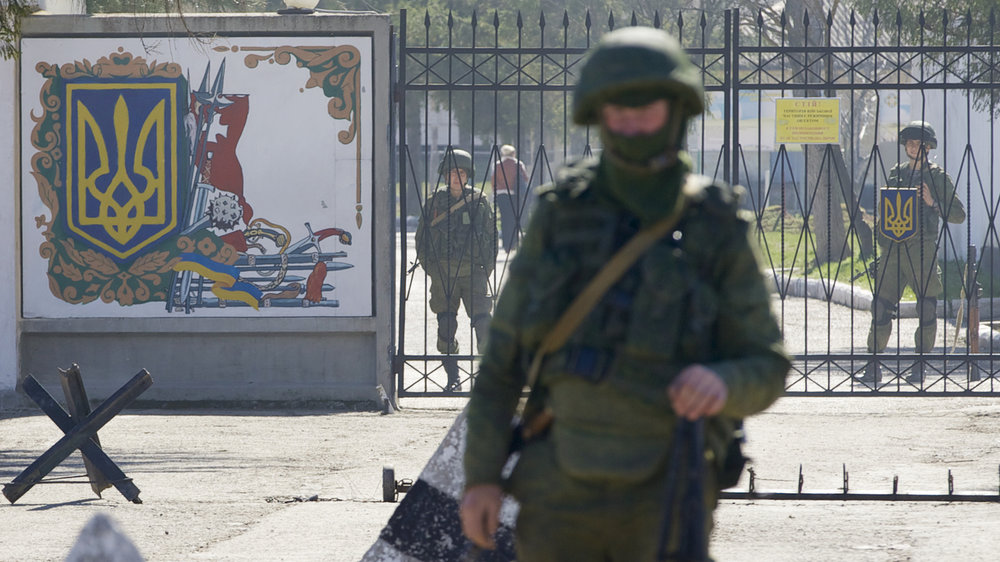 Russian soldiers guard the entrance to the Ukrainian military base in Perevalne, Crimea | Ivan Sekretarev/AP