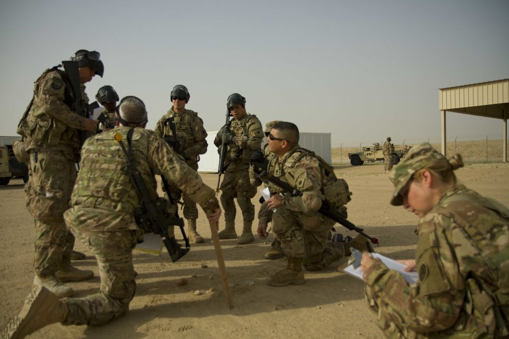 Staff Sgt. Jessica Spencer, a small group leader, from 640th Regional Training Institute attached to the U.S Army Central Noncommissioned Officer Academy, evaluates a squad leader's mission preparation at Camp Buehring, Kuwait. (U.S. Army Photo/Sgt. Youtoy Martin)