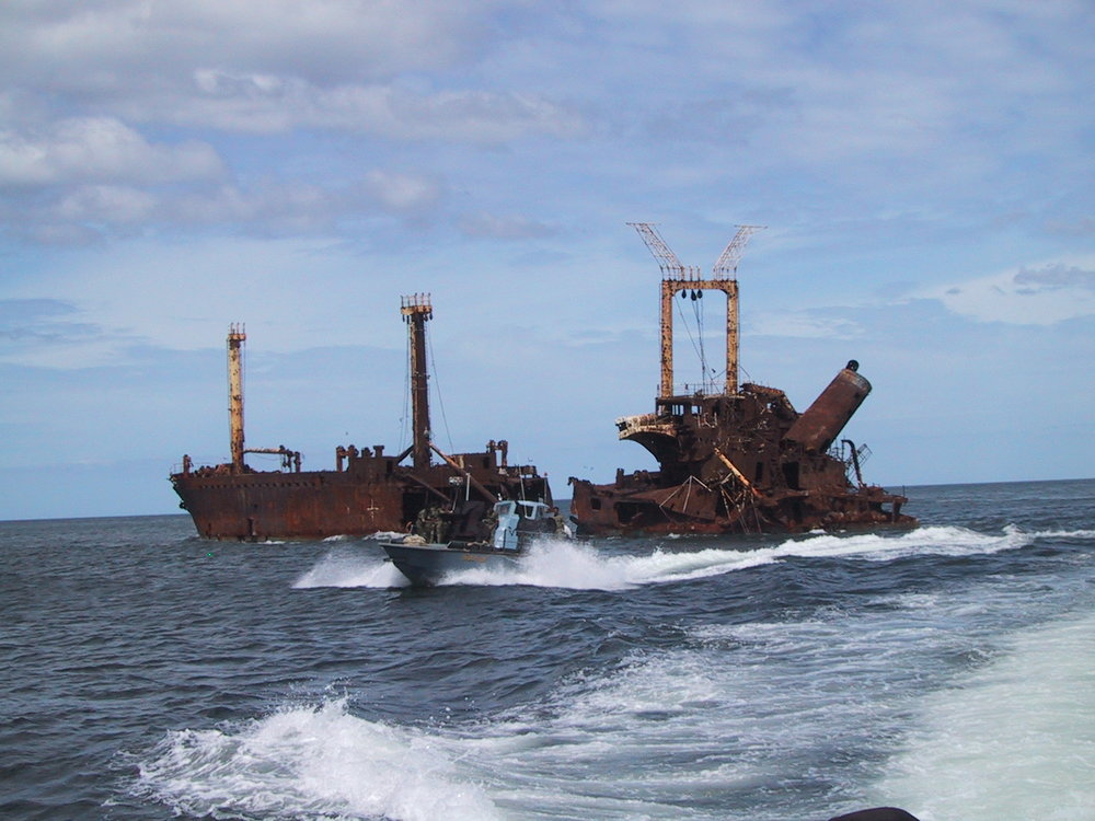 An LTTE Sea Tiger fast attack fiberglass boat passing a Sri Lankan freighter sunken by the Sea Tigers just north of the village of Mullaitivu, North-eastern Sri Lanka. (Isak Berntsen/Wikimedia)