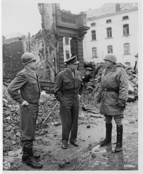 General Patton with Generals Eisenhower and Bradley surveying the damage in Bastogne, Belgium (National Archives)