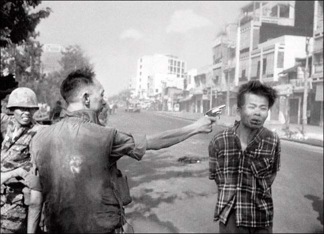 A communist guerrilla executed in a Saigon street during the Vietnam War. )Eddie Adams/New York Times)
