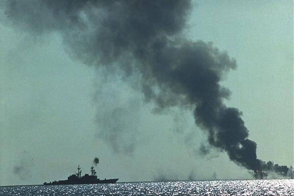 The U.S.S. Merrill (DD-976), operating as a part of Surface Action Group Bravo, shortly after a coordinated attack on the Sassan oil platform complex where Iranian based forces for attacks on Iraqi and Kuwati merchant vessels. (Wikimedia Commons)