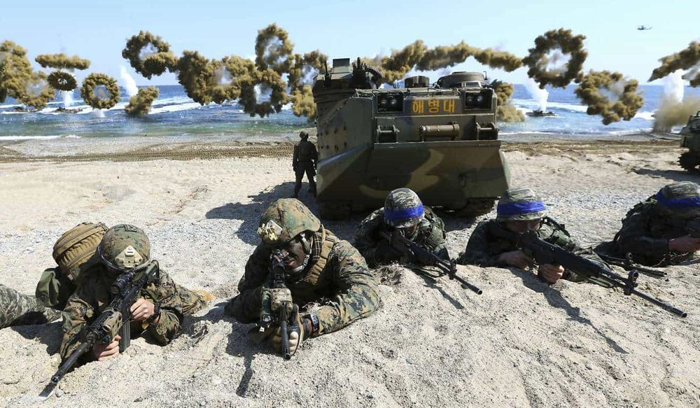 U.S. Marines, left, and South Korean Marines, wearing blue headbands on their helmets, take positions after landing on the beach during the joint military combined amphibious exercise, called Ssangyong, part of the Key Resolve and Foal Eagle military exercises, in Pohang, South Korea. (Kim Jun-bum/Yonhap/AP)