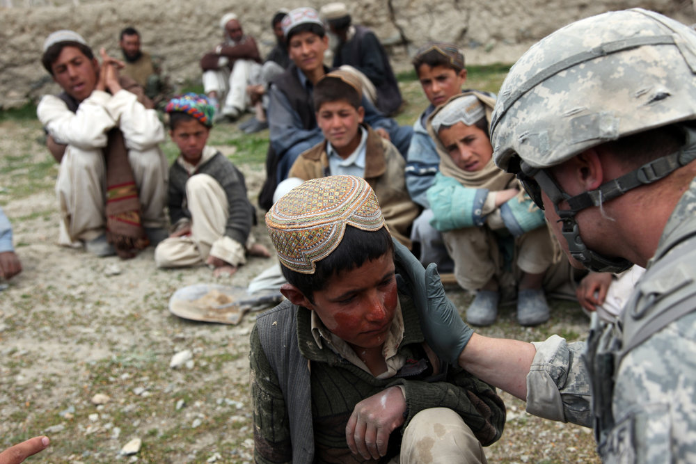 A U.S. Army medic treats an Afghan child for a sunburn in the village of Meryanay Kherwar District, Logar province, Afghanistan, April 9. (ISAF Public Affairs Photo/Wikimeida)