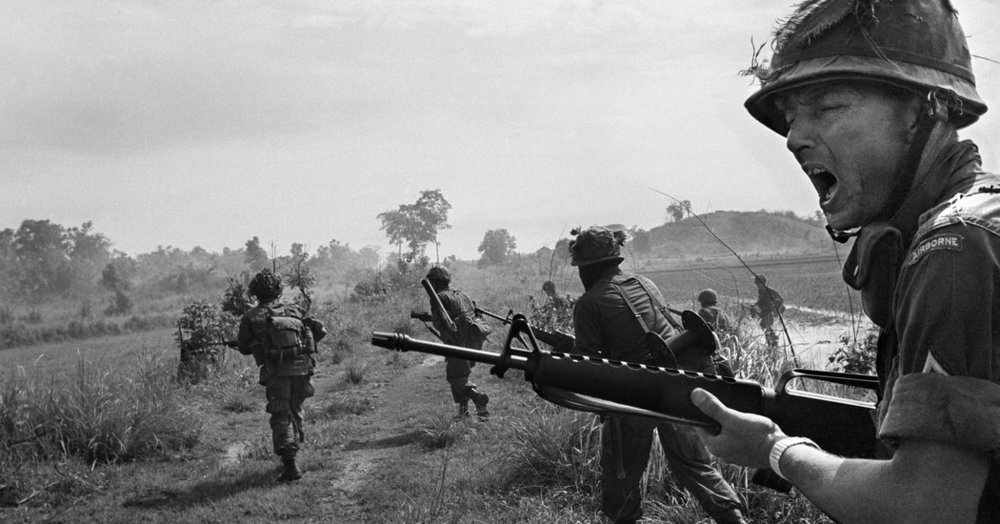 An American paratrooper sergeant shouts orders to his squad as they charge brush line while subject to sniper fire in Vietnam on June 1, 1965. Horst Faas | Associated Press