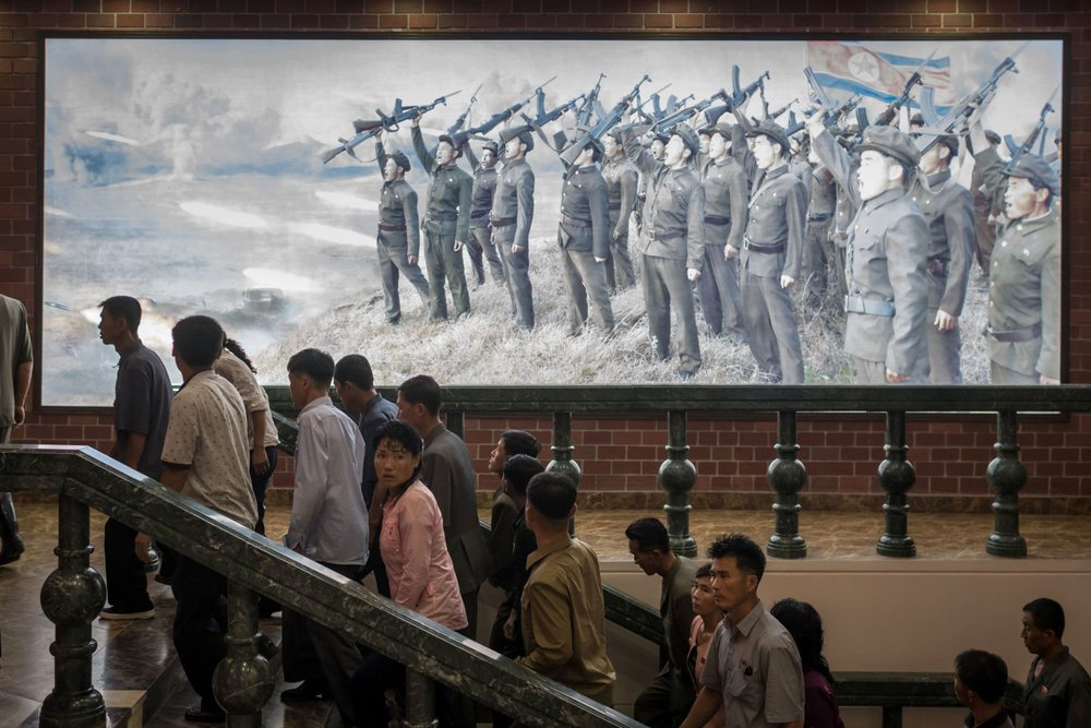 People walk up stairs near a propaganda poster depicting Korean People's Army soldiers at a museum in Sinchon, south of Pyongyang | AFP-JIJI.