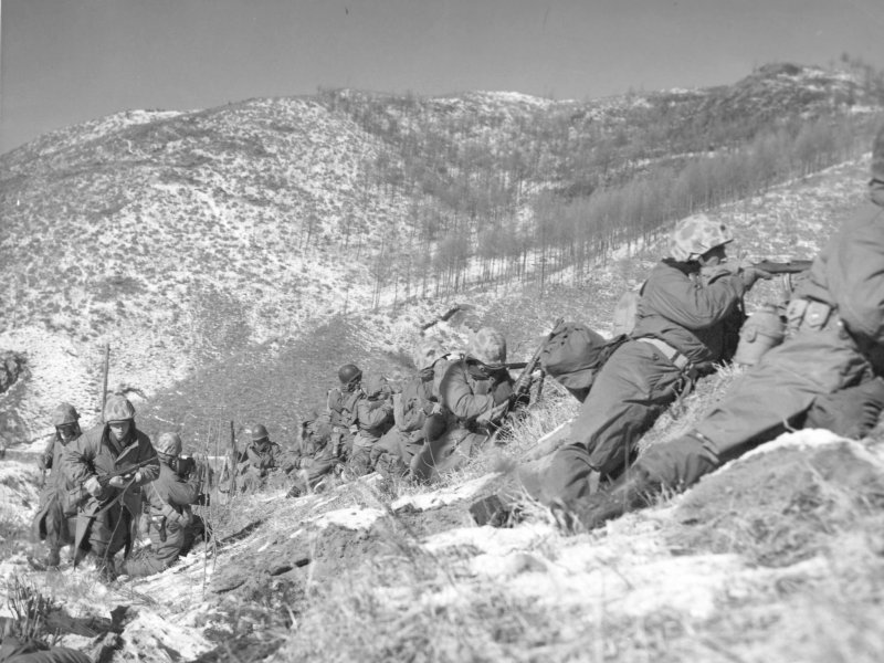 Marines under cover of large boulder engage enemy forces who were unsuccessful in trapping the Marines | Wikimedia Commons