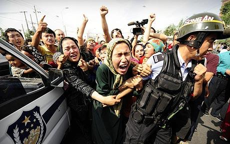 Ethnic Uygur women grab a riot policemen as they protest in 2009. (AFP)
