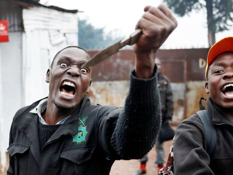 An opposition supporter gestures with a knife during clashes with police in Nairobi, Kenya. (Goran Tomasevic/Reuters)