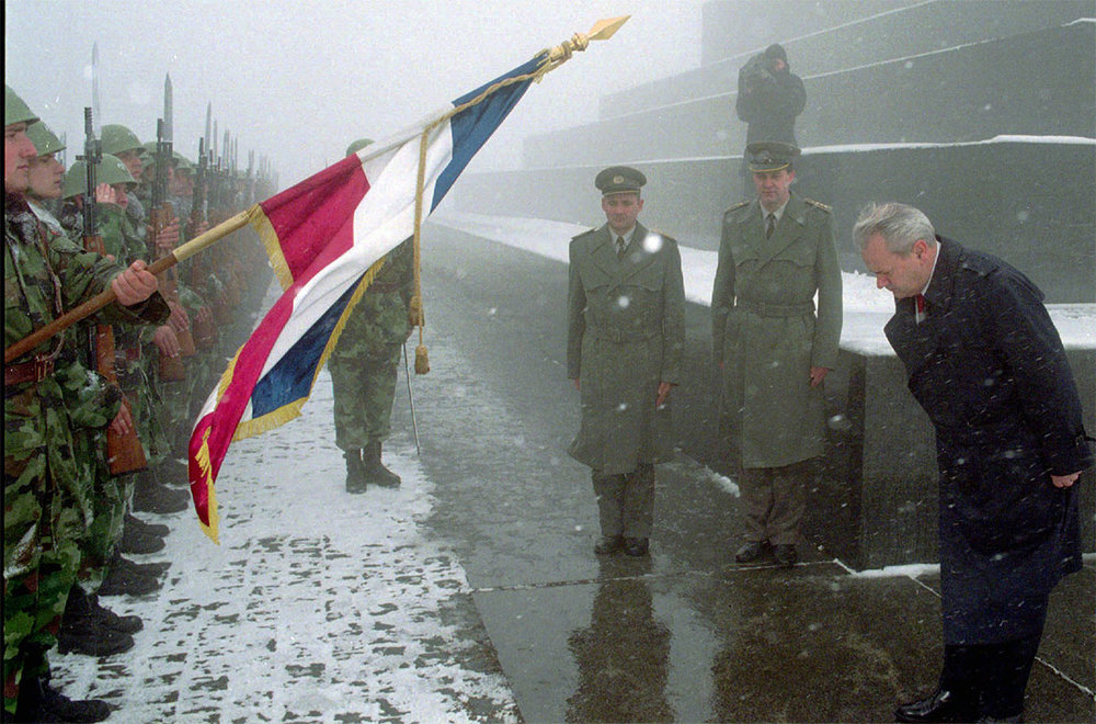 Serbian President Slobodan Milosevic bows to the Serbian flag during a ceremony at Belgrade's Monument To The Unknown Soldier in 1996. (AP)