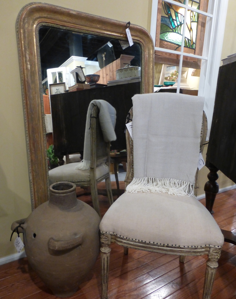 1830's Louise Philippe Mirror propped behind a mid 20th century chair in the Empire style and a 1880's Provencal jar.
