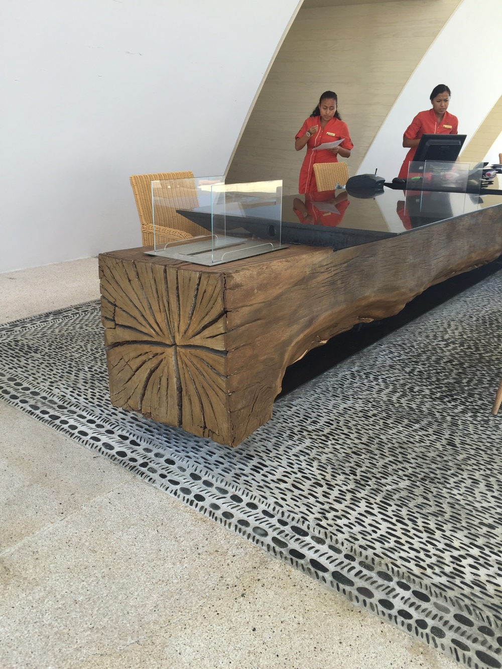 The reception desk was one huge natural log resting on a magnificent stone inlaid floor.
