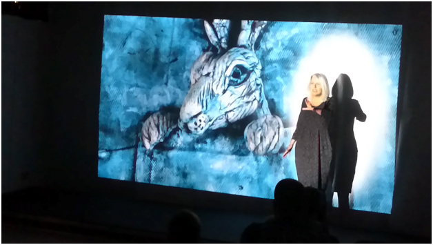 Jacqueline Harris telling the story of the White Dobbie with a projected image of Hare in my Pocket