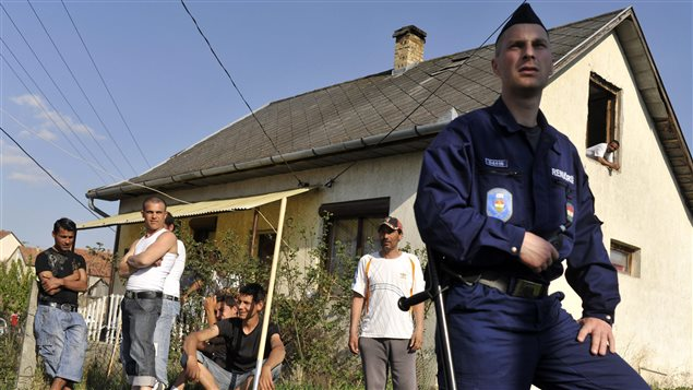 In April 2011, a Hungarian police officer guarded a Roma neighbourhood close to a site where vigilante groups set up a training camp. Threats from vigilantes and discrimination prompted some Roma to flee Hungary. Photo Credit: Bela Szandelszky/AP Photo