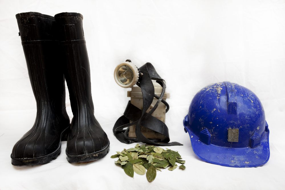The miners' most important gear. From left, clockwise: steel-toed rain boots, a lamp, helmet, coca leaves.