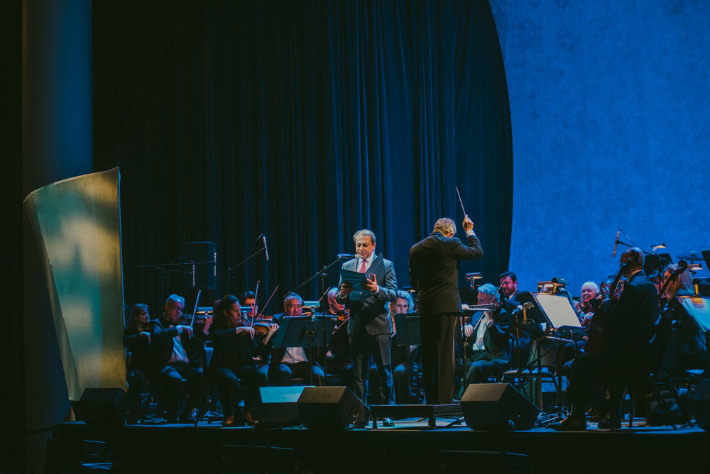"Preet Bharara reads the stirring words of Abraham Lincoln as the Knickerbocker Chamber Orchestra, conducted by Gary S. Fagin, performs Aaron Copland's ""Lincoln Portrait"" as part of the Renaissance & Renewal concert on February 10, 2018 in the Winter Garden, Brookfield Plaza. Photo credit: Ryan Muir, courtesy of Arts Brookfield."
