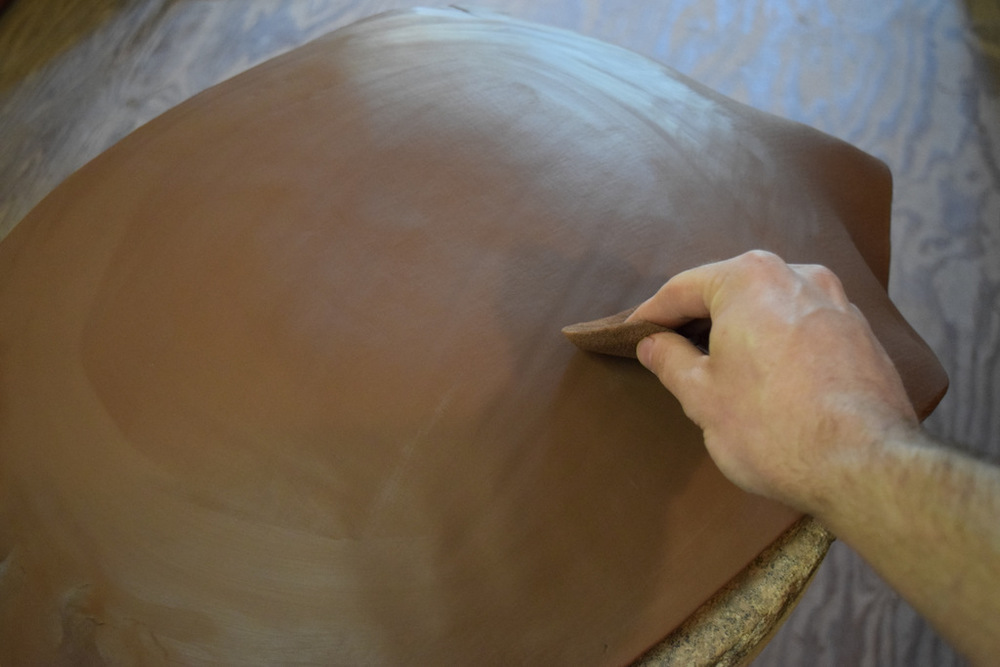 smoothing the clay with a sponge