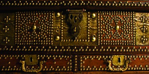 In the majority of local (Southern Arabia) households prior to the start of modern development around 1950, chests were the only form of furniture and therefore are one of the few truly indigenous antiques. Not only did they form a functional purpose but were also used as a medium for the expression of decorative art.  Like the treasures they once held within their dark and woody depths, the beautiful hand made chests once used during the past several centuries across the Arabian peninsular, are becoming more rare with each passing year. No two chests are exactly alike and every one should be considered a work of art in its own right.  The oldest chests available at Showcase date back to the arrival of the Portuguese in Oman in the early 16th century. Made of Brazilian mahogany and often secured with a complex iron clasp and lock, they belonged to Portuguese officers, administrators and traders and were used to store personal possessions and weapons. When the explorers returned home they frequently left the chests behind - a reminder of their presence in that area. The Omanis later copied the style, including the small covered compartments on the inside, however, adjustments were made accordingly. They used teak, rosewood and jackfruit wood instead of mahogany and decorated the chests with dark wood beading, brass flowers, emblems and flat-pressed brass plates with Islamic patterns reflecting the inherent culture of the area.   The prized Mandoos chest was the most highly decorated with three or sometimes four drawers at the base and is referred to as a 'wedding chest'. It is possible to categorise chests by design such as Shiraz, Surat, Bombay, Malibar. These titles are not indicative of the origin but rather reflect their style and therefore they are better categorised by use such as wedding, domestic storage, sea or pearl chests.  All our antiques come with a certificate of authenticity stating full description and date.
