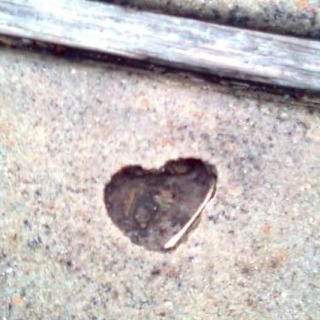 Photo credit goes to my son, Gavin, who was 12 when he found this heart shaped hole in concrete filled with water.  - Sugar Land, TX 2009