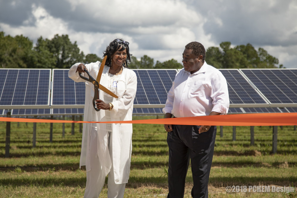 Loretta Slater, with Rev. Leo Woodberry, prepares for the ribbon-cutting to dedicate the Solar Facility to her daughter.