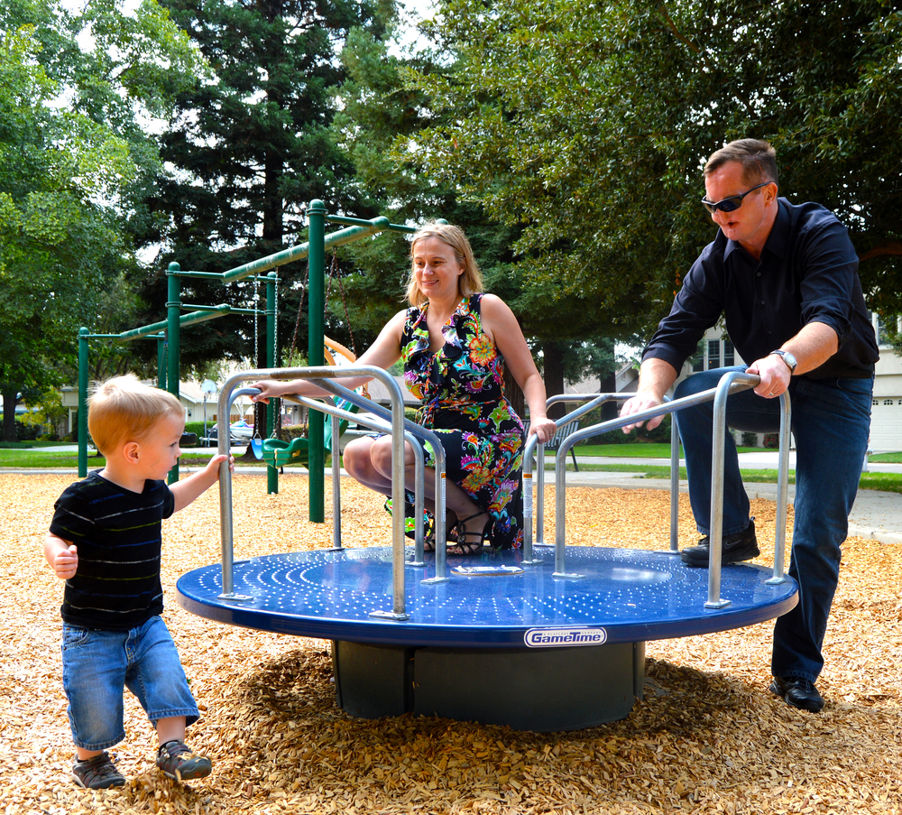 Photograph of Stacy and Greg playing with their son, Leo, on a park carousel.