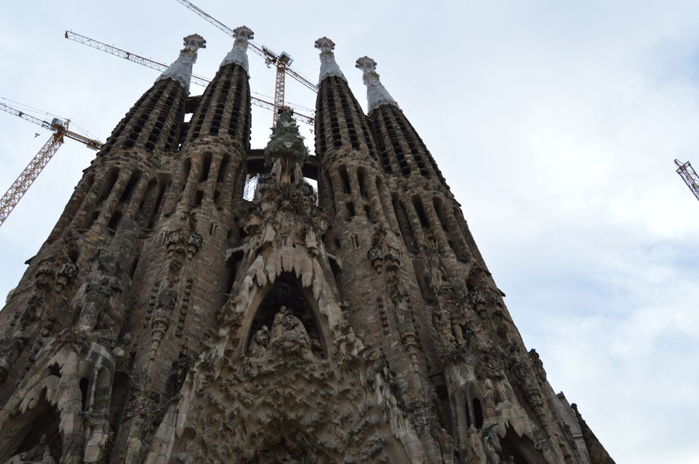 "This is called the ""Birthing Facade"" and depicts the birth of Jesus. The facade on the other side, which you might think looks similar because of the towers, actually depicts Jesus' crucifixion and death. Gaudí only lived to see part of this facade completed. The other facade is much newer. Photo by Max Siskind."