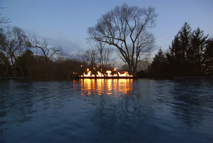 A linear fire trough made from corten steel seems to sit magical on top the calm water