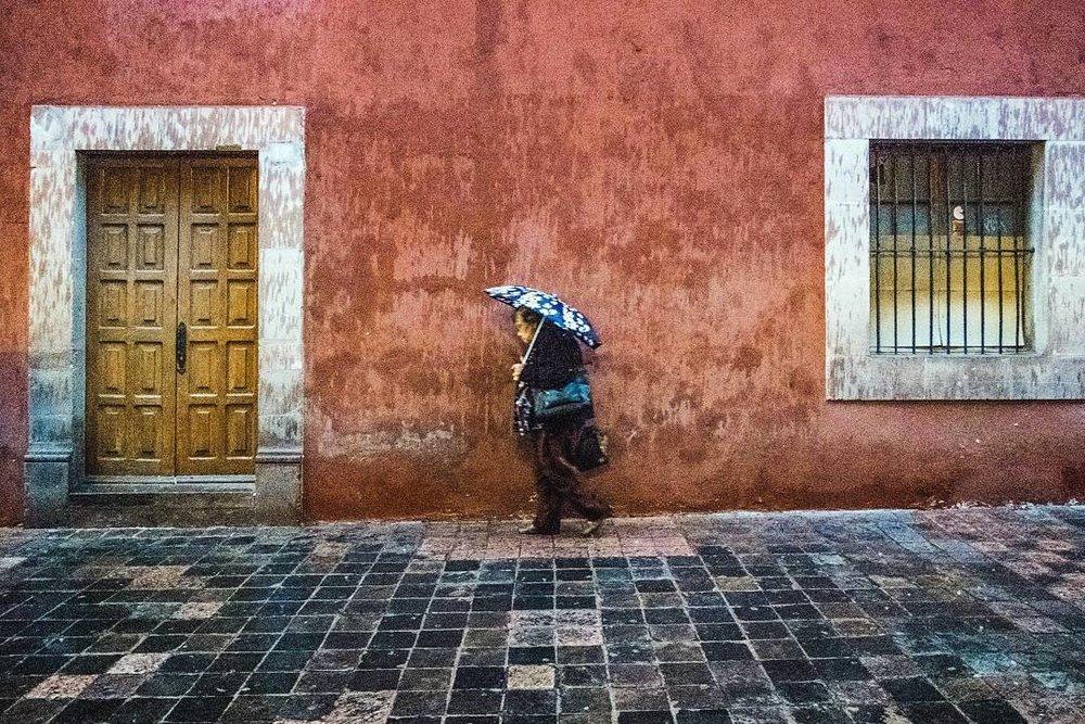 Esta imagen tomada por mi representa el cliché básico de la fotografía de calle: una persona caminando en la banqueta de enfrente (con una sombrilla). Es una imagen fácil de entender, sin mayor profundidad, que seguramente será olvidada por las gente en el mar de fotos similares que a diario se toman en el mundo.
