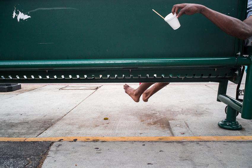 Esta foto por Tavepong Pratoomwong me gusta mucho por que roza el límite de lo incomprensible, puede llevar un poco de tiempo al espectador conectar la mancha blanca de la banca con el vaso que parece haberla lanzado y el brazo que lo sostiene con los pies detrás de la banca.