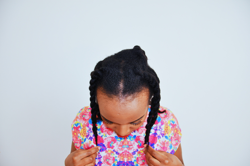 "What's my hair texture? In this picture, my two strand twists appear to lay flat on my head, but that doesn't mean that my hair is automatically ""fine"". It simply means that I've bundled my strands together. Hair width is genetic and does not change depending on a hair style."