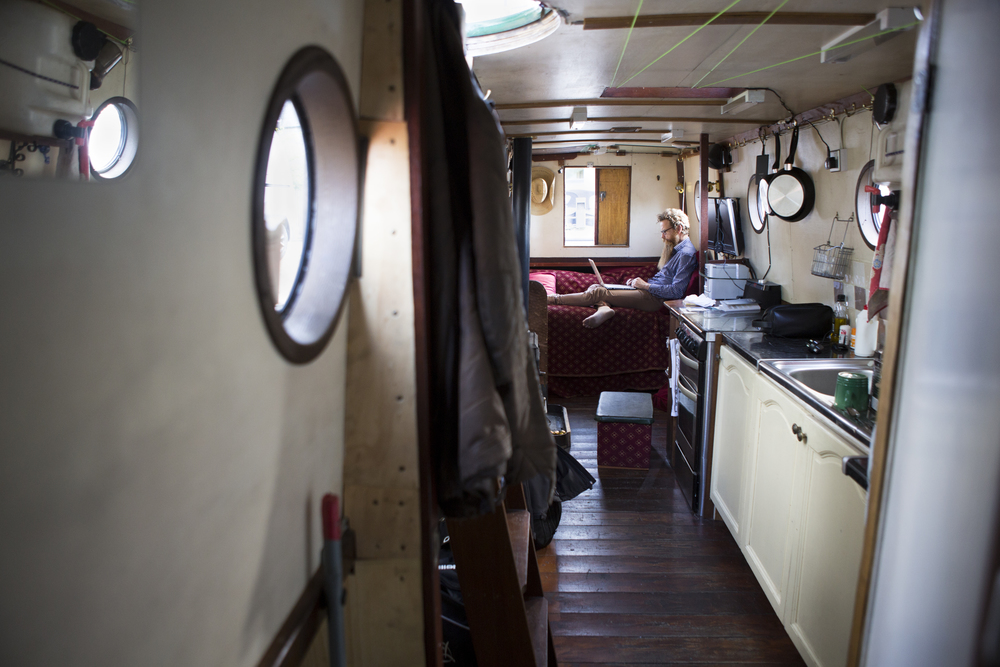 Nic Boyes works on his laptop in his houseboat along the Union Canal in Edinburgh, Scotland on August 1, 2015. Boyes has lived in a houseboat for several years and said he likes the freedom it affords him in moving around.